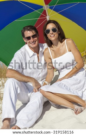 Man and woman romantic couple under a multi colored sun umbrella or parasol on a beach