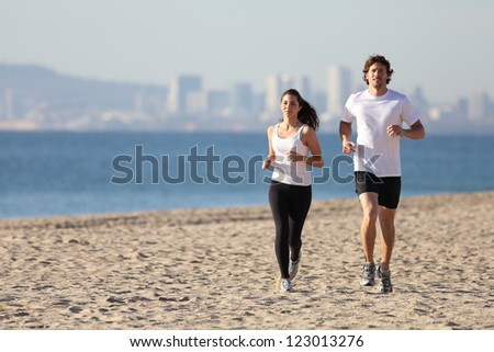 Man and woman running in the beach towards the camera with a city in background