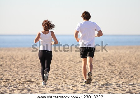 Man and woman running in the beach towards the sea - stock photo