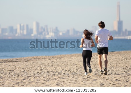 Man and woman running in the beach towards the sea with a city in background