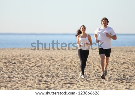 Man and woman running towards camera in the beach smiling