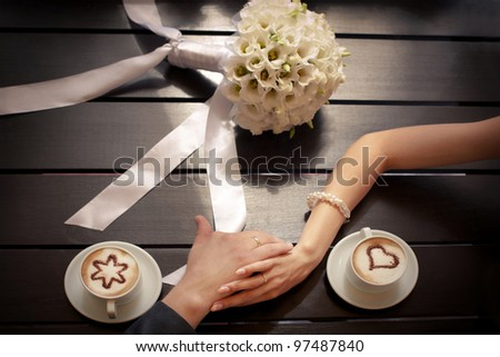 Man and woman's hands and coffee cups on the table - stock photo