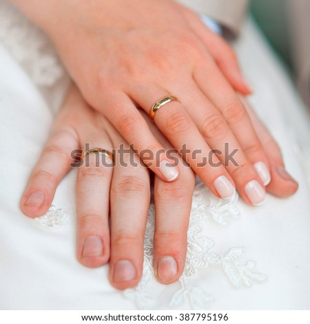 Man and woman's hands with wedding rings and wedding dress. Bride and groom holding hands with wedding rings. - stock photo