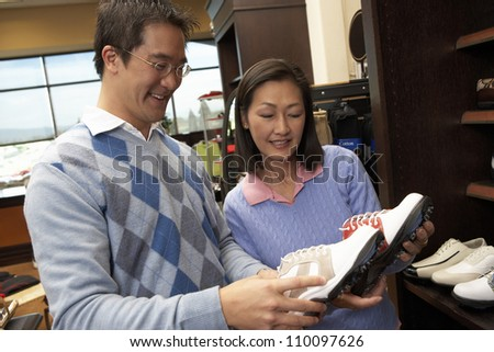 Man and woman selecting shoes in store - stock photo