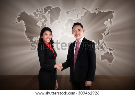 Man and woman shaking hand with world map as background
