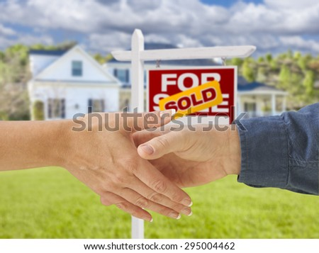 Man and Woman Shaking Hands in Front of a Beautiful New House and Sold For Sale Real Estate Sign. - stock photo