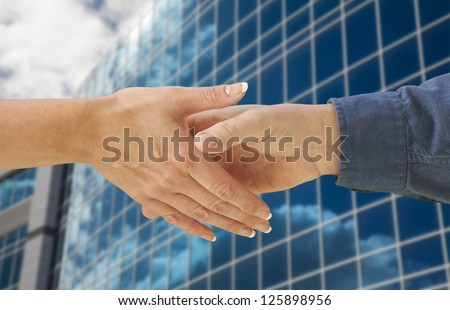 Man and Woman Shaking Hands In Front of Corporate Building Background. - stock photo