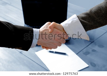 man and woman shaking hands in front of laptop - stock photo