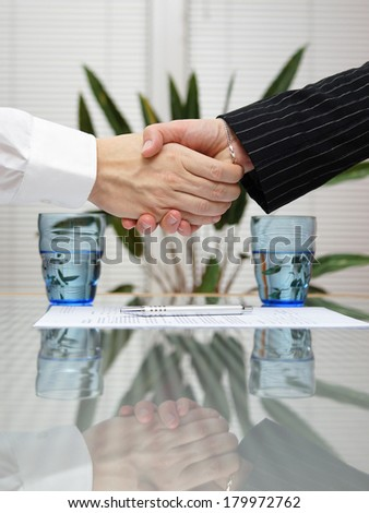 man and woman shaking hands over signed insurance - stock photo