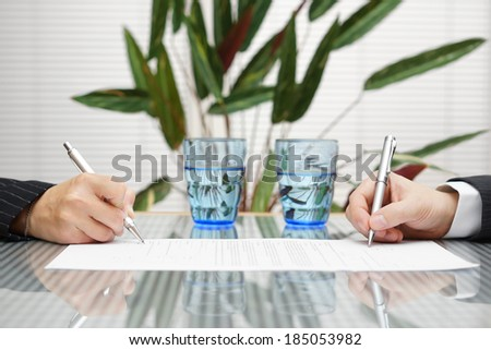 man and woman signing document with divorce or prenuptial agreement - stock photo