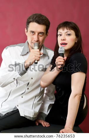 Man and Woman Singing Karaoke on red burgundy background - stock photo