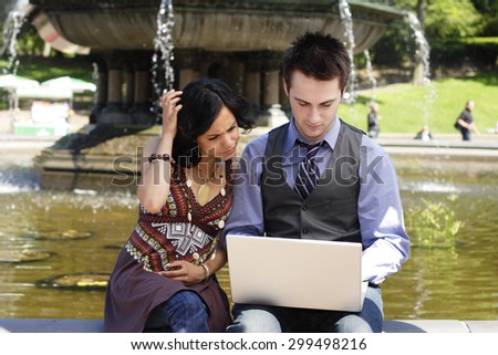Man and woman sit at fountain looking at laptop. - stock photo