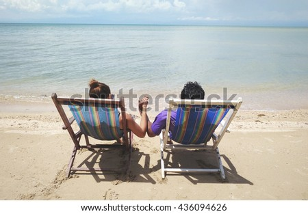 Man and Woman sit on beach chair, couple of hands against the sea view - stock photo