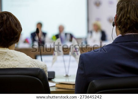 Man and woman sitting at a round table in the negotiations in the conference room - stock photo