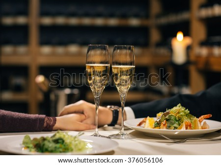 Man and woman sitting in a restaurant by a table and holding glasses with wine