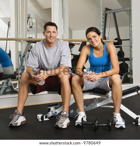 Man and woman sitting on exercise machine smiling holding water bottles. - stock photo