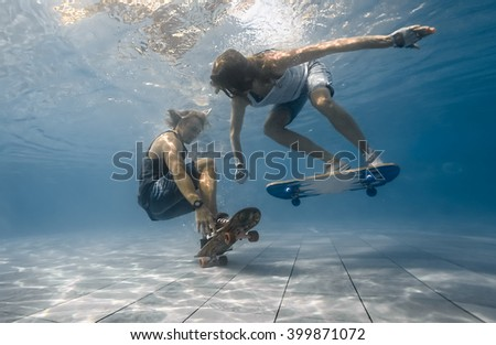 Man and Woman skateboarding underwater in the swimming pool - stock photo