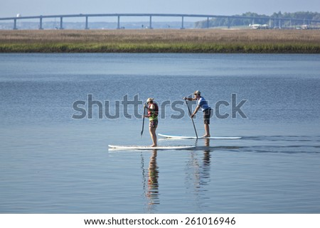 man and woman stand up paddleboarding - stock photo