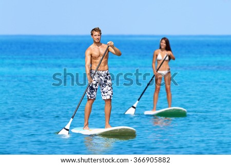 Man and woman stand up paddleboarding on ocean. Young couple are doing watersport on sea. Male and female tourists are in swimwear during summer vacation. - stock photo
