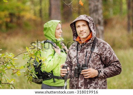 Man and woman standing alone in forest outdoor with sunset nature on background. Travel Lifestyle and survival concept - stock photo