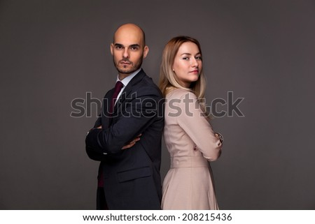Man and woman standing back to back - stock photo