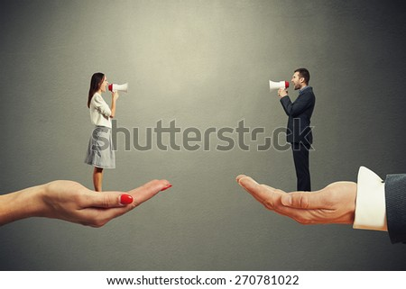 man and woman standing on the big palms and screaming at each other over dark background - stock photo