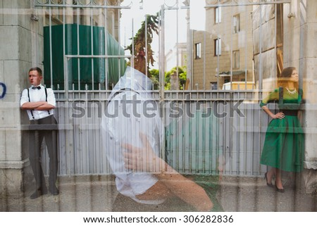 man and woman standing on the street on the opposite sides of the gate - stock photo
