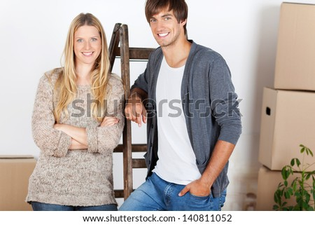 man and woman standing with ladder and boxes - stock photo