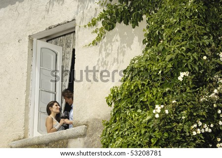 man and woman talking appearing at a window - stock photo