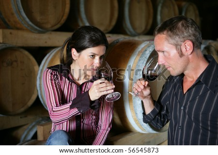 Man and woman tasting a glass of red wine - stock photo