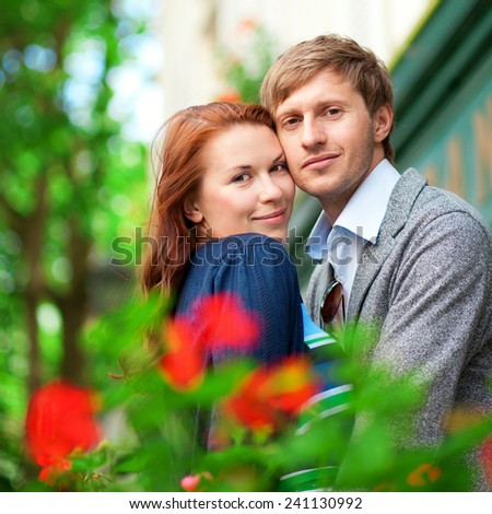 Man and woman together on balcony with blossoming geranium - stock photo