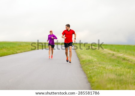 Man and woman two people runners running on country road, healthy fitness lifestyle, sport speed training beautiful landscape. Young couple doing workout exercising walking outdoors in nature. - stock photo