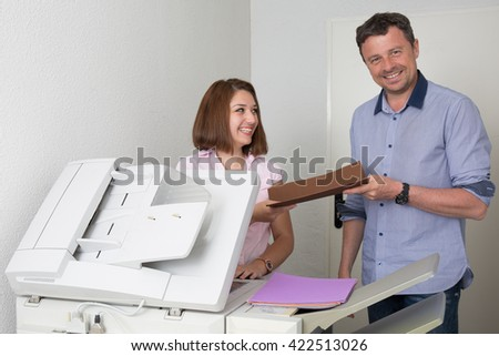 Man and woman using a copy machine at office