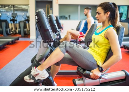 Man and woman using exercise machines at the gym