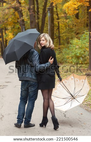Man and woman walk under umbrellas in autumn park - stock photo
