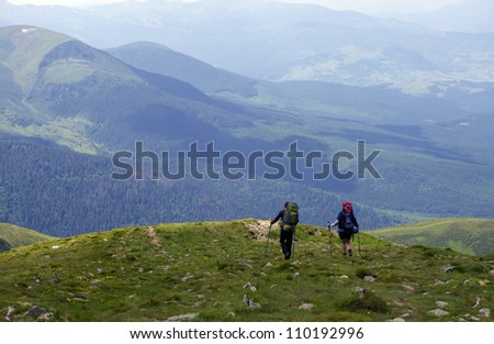 man and woman walking in the mountains - stock photo