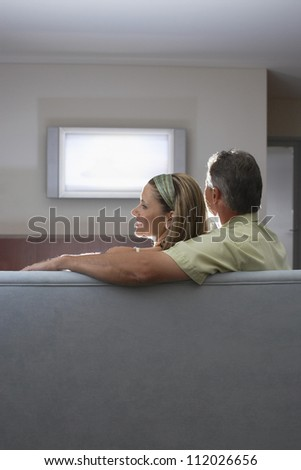 Man and woman watching television together at home