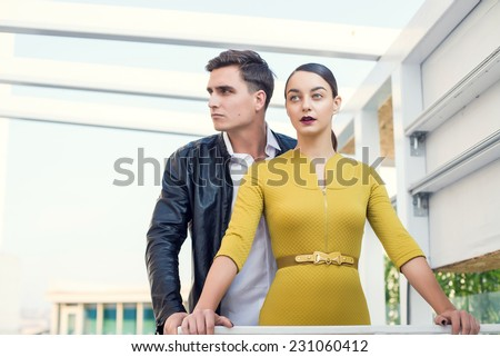 Man and woman wearing classic clothes, him in white shirt and leather jacket, her in yellow dress standing together with the business center on the background. Outdoor fashion shot. - stock photo