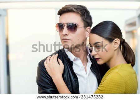 Man and woman wearing classic clothes, him in white shirt and leather jacket, her in yellow dress jacket standing together with the business center on the background. Outdoor fashion shot. - stock photo