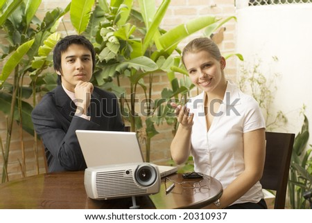 Man and woman with a projector and a laptop. They are seated and she is smiling while he looks pensive. Horizontally framed photo. - stock photo