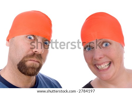 Man and woman with an orange swim caps making a funny faces - stock photo