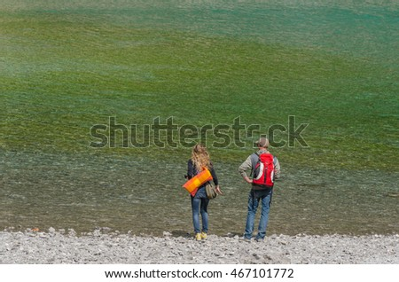 man and woman with backpack standing on the lake