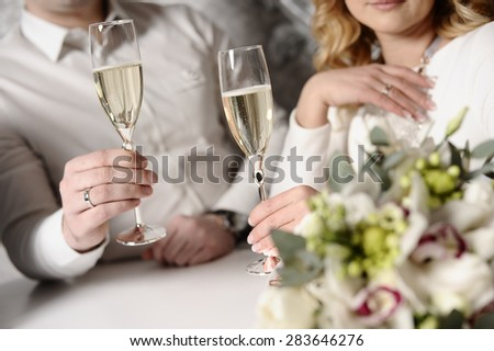 Man and woman with glasses of champagne in hand. - stock photo