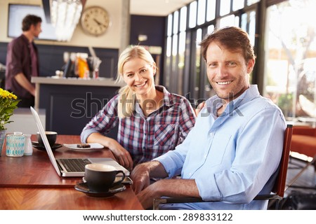 Man and woman with laptop at a coffee shop - stock photo
