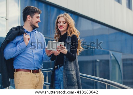 Man and woman with tablet in the city. - stock photo