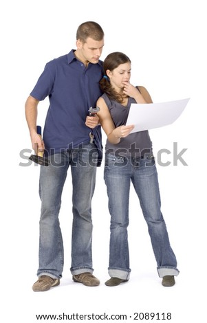 man and woman (workers) standing with tools and house plan - stock photo