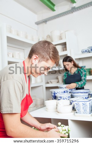 Man and woman working in a ceramics shop