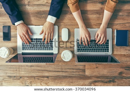 man and woman working on their computers. the view from the top. two laptops, two persons. - stock photo