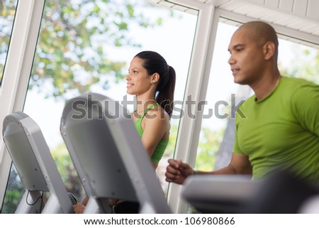 Man and woman working out and running on treadmill in fitness club - stock photo