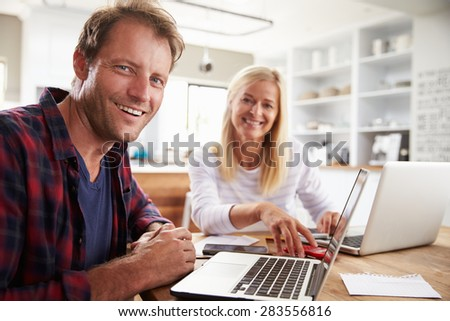 Man and woman working together at home - stock photo